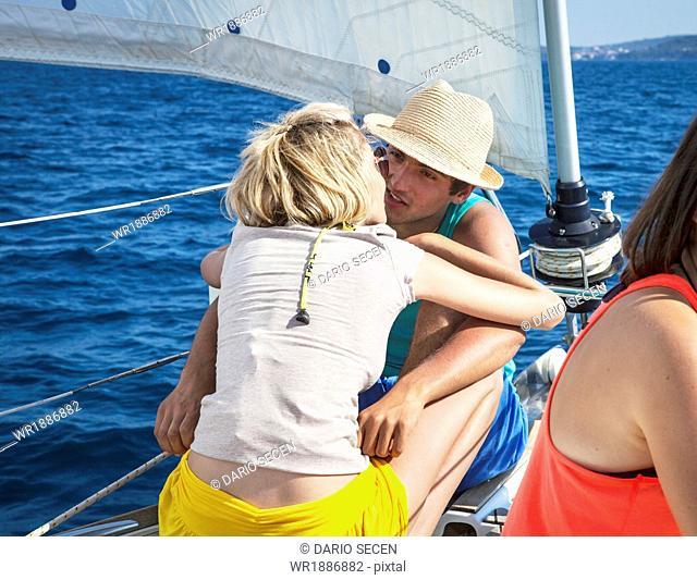 Croatia, Adriatic Sea, Young couple on sailboat kissing