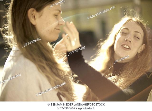 woman slapping friendly man in face, outside in sunlight, in Berlin, Germany