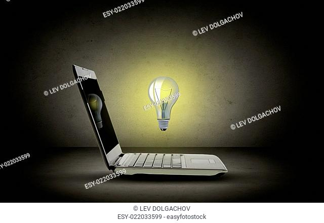 technology, business, startup and idea concept - open laptop computer with lighting bulb over dark gray background