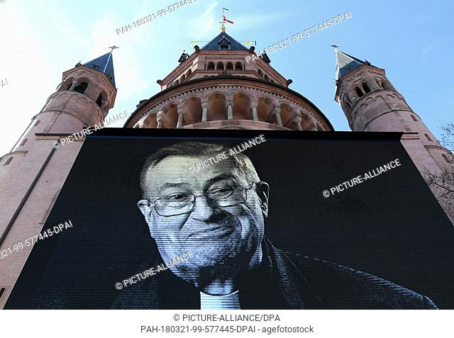 21 March 2018, Germany, Mainz: A picture of Cardinal Karl Legmann can be seen on a screen outside the Mainz Cathedral. The funeral of the former bishop of Mainz