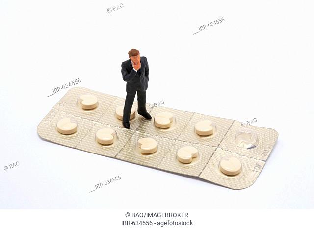 Small man standing on a large pill packet (beta blockers): symbol for skepticism of the pharmaceutical industry