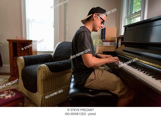 Teenage boy sitting playing piano in dining room