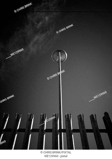 Black and white image of a street light behind spikey fence in Cheshire, England, UK, Europe