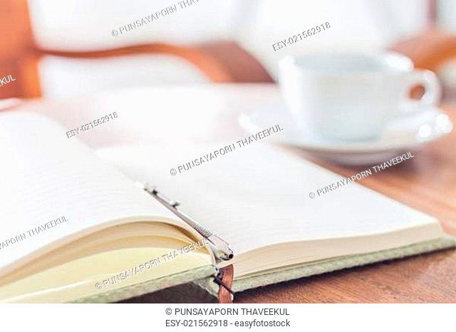 Open a blank white notebook and pen with a cup of coffee