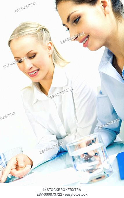 Vertical image of smart woman pointing at paper while another one looking at it