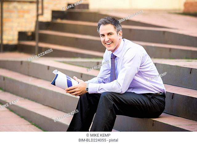 Caucasian businessman sitting on staircase holding paperwork
