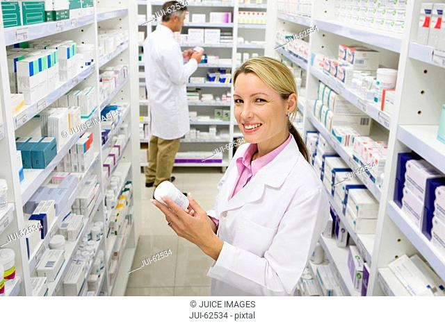 Pharmacist holding bottle of prescription medication in pharmacy