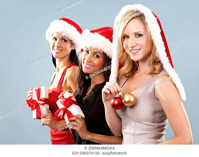 beautiful three women wearing christmas hats on blue background
