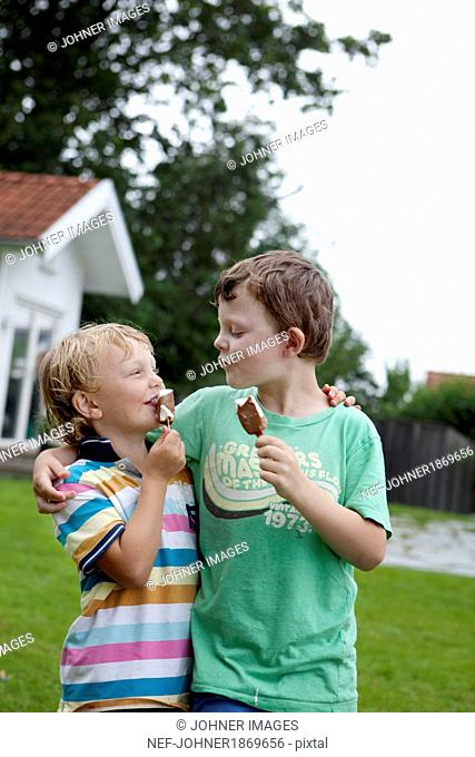 Brothers holding ice cream and looking at each other