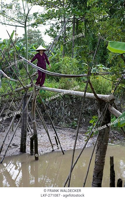 Vietnamese woman walking over a pile bridge in the Mekong Delta, Can Tho Province, Vietnam, Asia