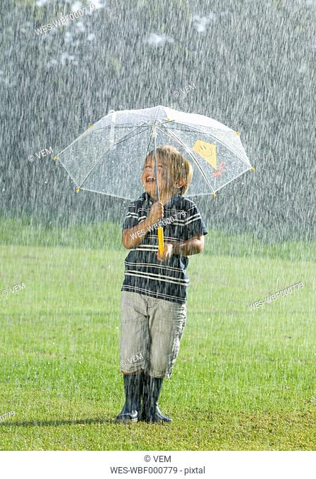 Boy standing with umbrella in rain