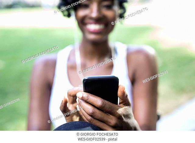 Woman using cell phone in a park, close-up
