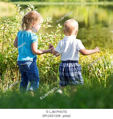 Young brother and sister walking together on shore; Edmonton, Alberta, Canada