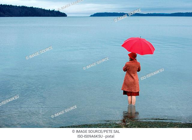 Woman with umbrella in rural lake