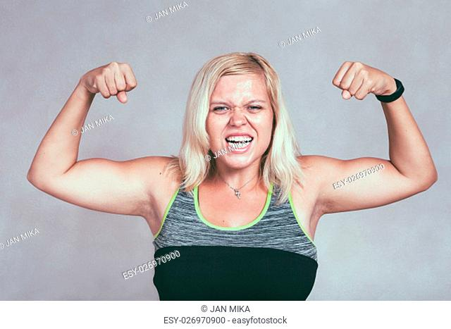 Strong excited muscular woman flexing her muscles. Young blond sporty female showing arms and biceps