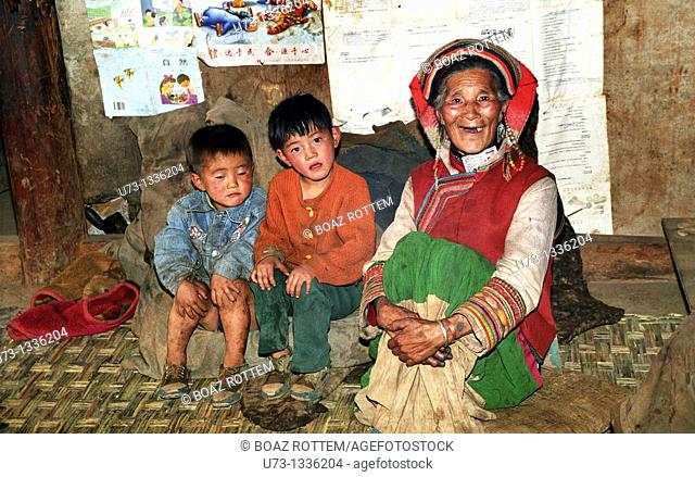 A happy Yi woman with her grandchildren inside her small home in rural Yunnan province, China
