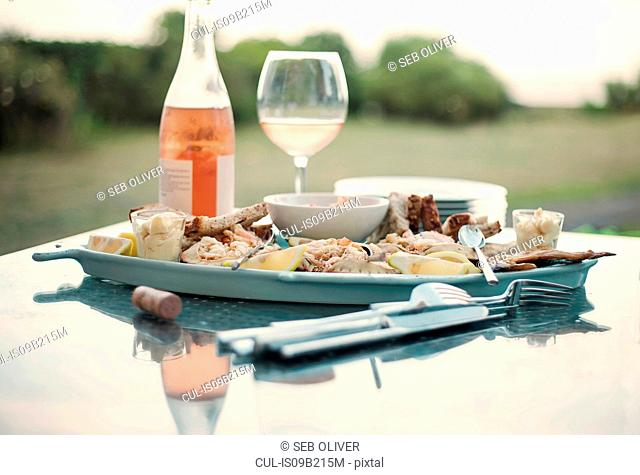 Tray of seafood and bottle of wine on table