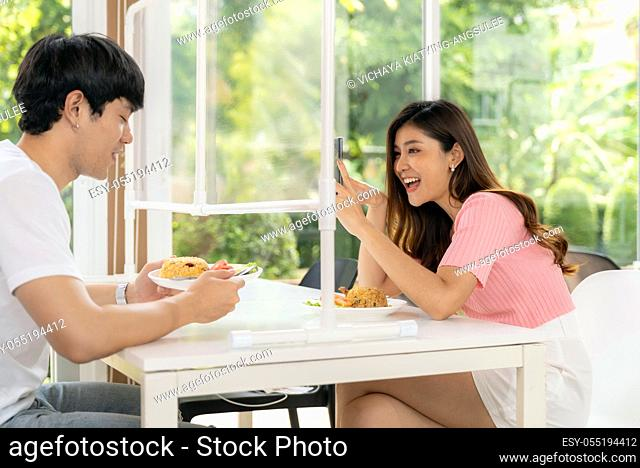 Asian young couple eating out together at new normal social distance restaurant. Woman take photo as food blogger influencer or vlogger through table shield...
