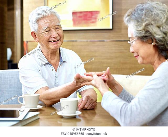senior asian woman trying to read the palmistry of her husband while having coffee together