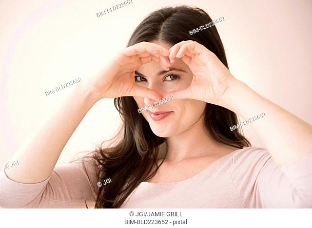 Caucasian woman gesturing heart-shape with hands over eyes