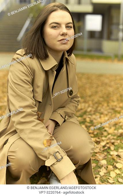 young woman crouching outdoors with autumn leaves, wearing coat, in Munich, Bavaria, Germany