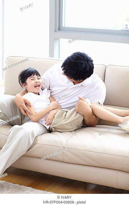 Father And Daughter Playing On Couch