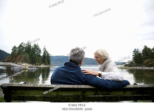 Senior couple laughing on bench overlooking lake