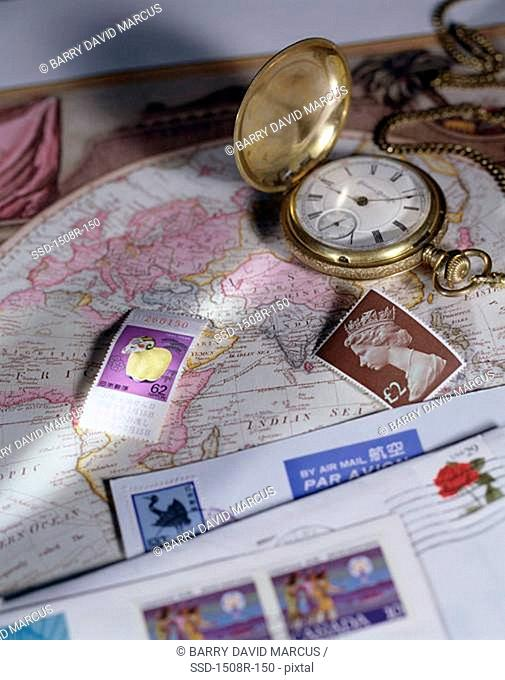 Close-up of a pocket watch on a map