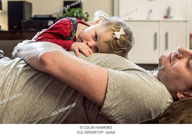 Daughter lying on fathers chest
