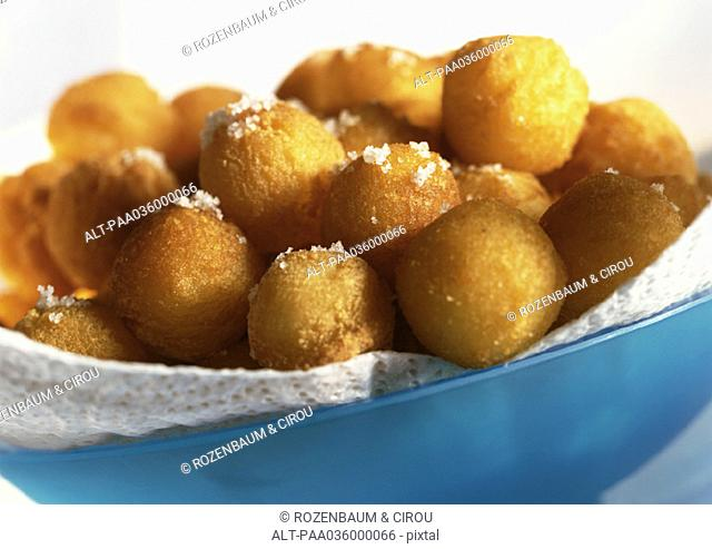 Bowl of dauphine potatoes sprinkled with sea salt, close-up