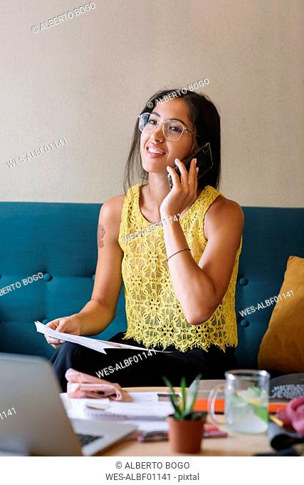 Smiling fashion designer sitting on couch talking on the phone