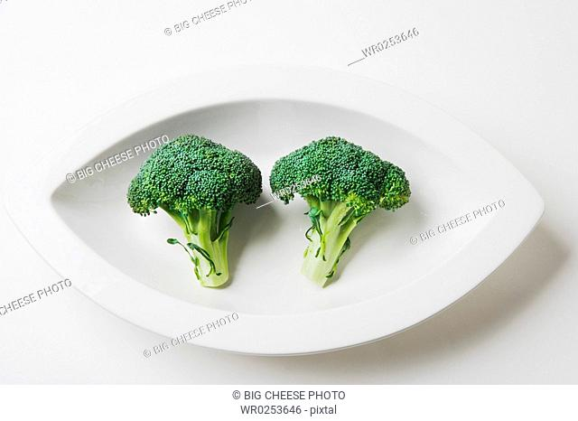 Two broccoli crowns in a dish