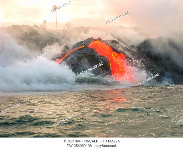Sea view of Kilauea Volcano in Big Island, Hawaii, United States. Shot taken at sunset when the lava glows in the dark as jumps into the sea