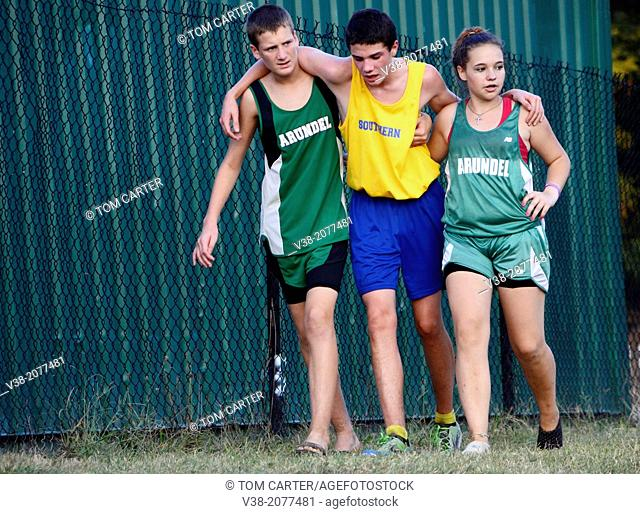 2 teens from a competing school help an injured student who was injured in a cross country match in Harwood, Md