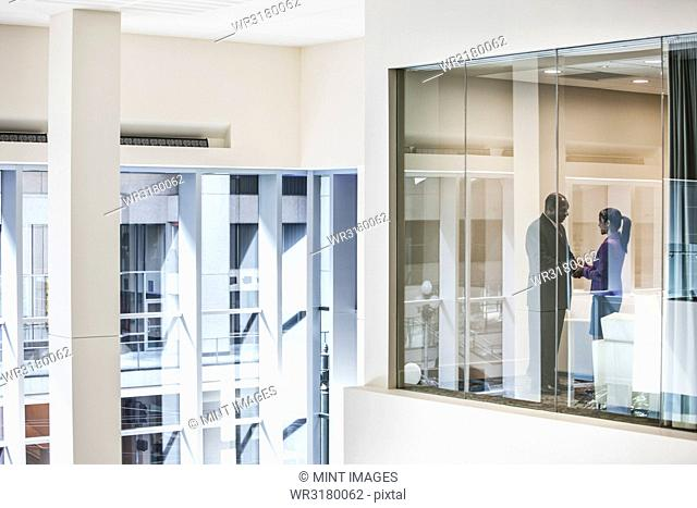 Black businessman and woman shaking hands in conference room window
