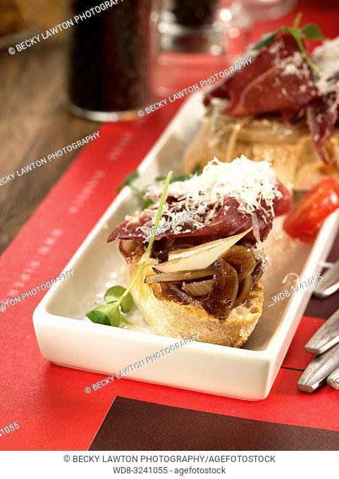 montadito de cecina con cebolla macerada y queso parmesano