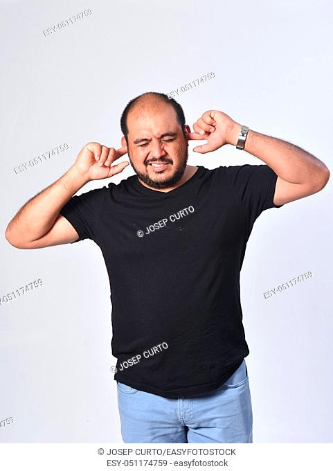 latin american man making noise hurting her ears on white background