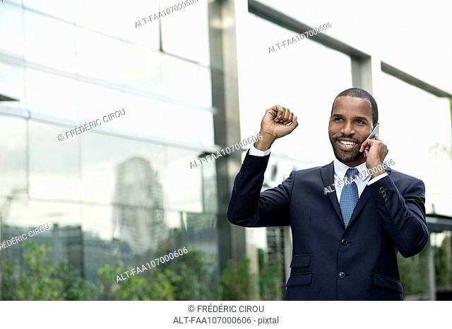 Businessman celebrating good news while talking on cell phone