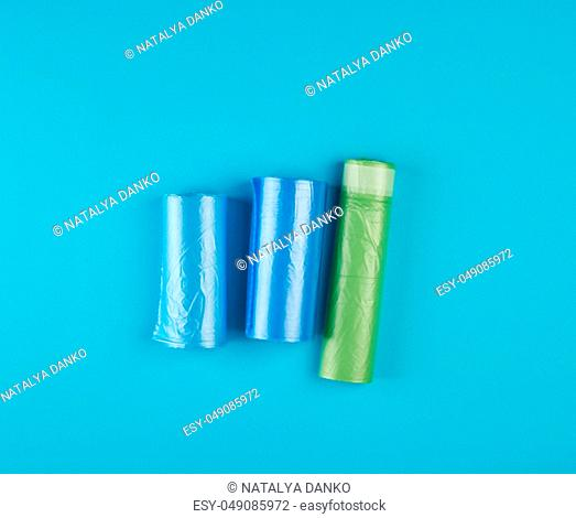 three rolled up rolls with plastic garbage bags on a blue background