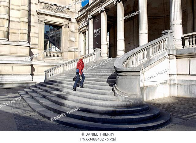 France. Paris 16th district. Woman climbing up the stairs of the Galliera palace, the museum of the fashion of the City of Paris