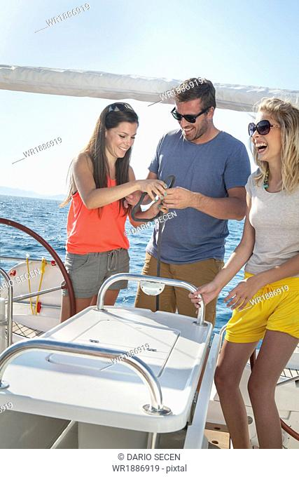 Croatia, Adriatic Sea, Young people on sailboat learn how to tie knots