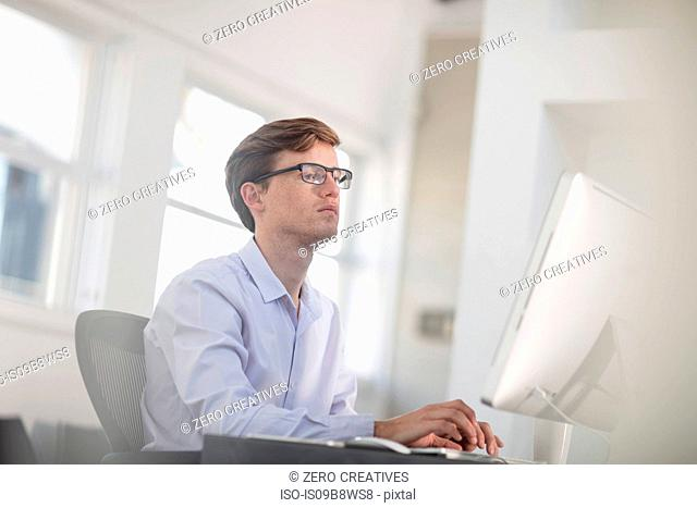Young male office worker typing at desktop computer