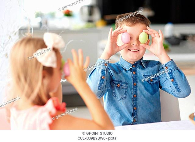 Girl with brother holding easter eggs over their eyes