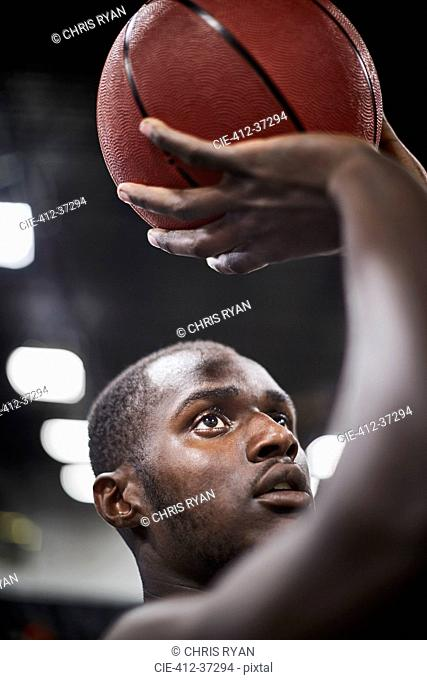 Close up focused young male basketball player shooting the ball