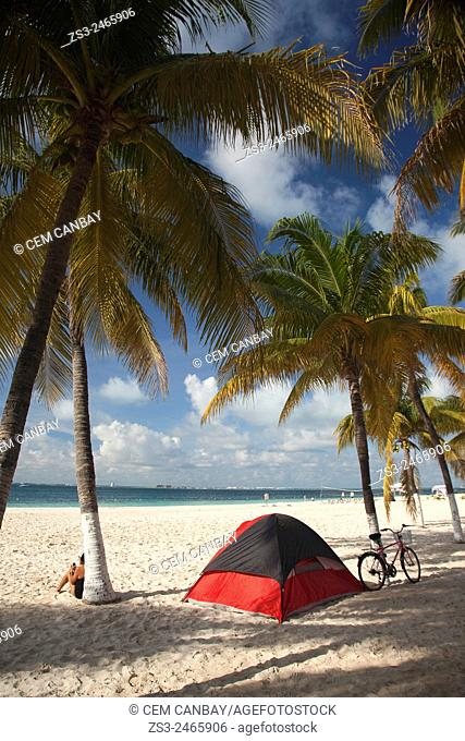 Woman sitting near her tent and bicycle under the palm trees at the beach of Isla Mujeres, Cancun, Quintana Roo, Yucatan Province, Mexico, Central America