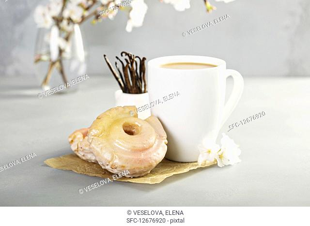 Vanilla old fashioned fried donuts with pink glitter glaze and a cup of coffee
