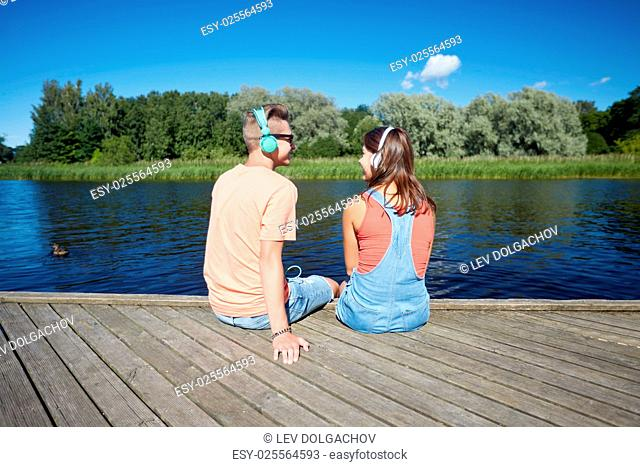 holidays, vacation, love and people concept - happy teenage couple with headphones sitting on river berth and listening to music at summer