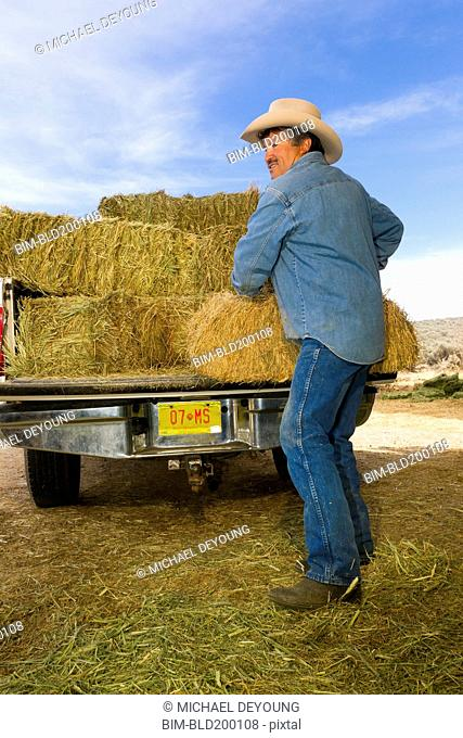 Hispanic man unloading hay from truck
