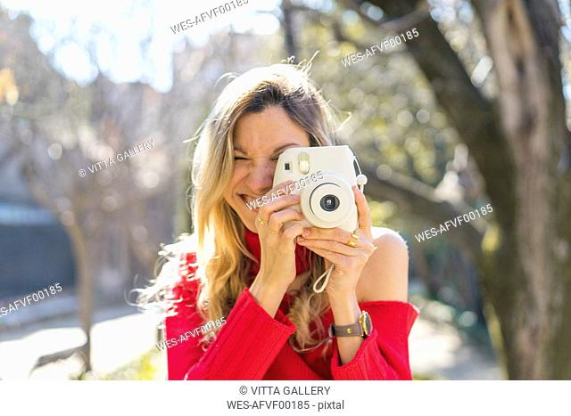 Happy young woman taking a picture in a garden