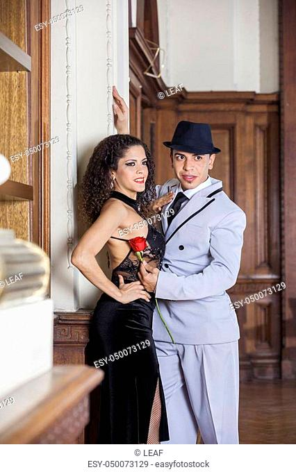 Young male and female tango partners looking away while performing in restaurant